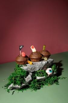 Lustige halloween-landschaft. schreckliche drohungen. cupcakes mit geleewürmern und fingern steht auf steinen und moos