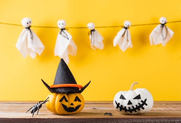 Lustige halloween-tagesdekorationsparty niedlicher geist bastelt beängstigendes gesicht hängen und kürbiskopflächeln