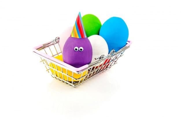 Lustige handgemachte eier im metalleinkaufskorb lokalisiert auf weiß