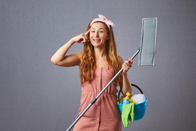 Lustige hausfrau, die mit einem mopp herum putzt und idee auf einer grauen wand hat. komische weibliche waschmaschine, die über das reinigen und halten von mopp, eimer, waschmittel und schwamm nachdenkt.