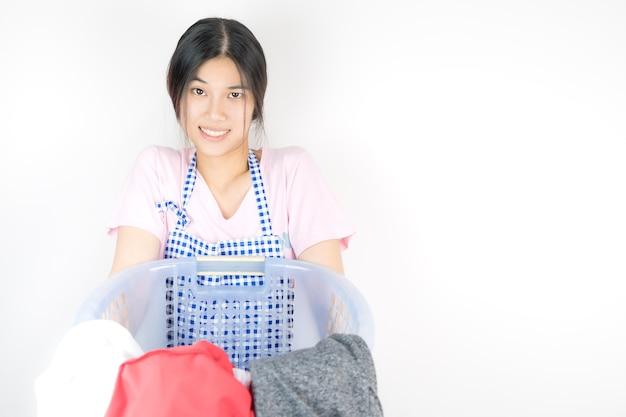Lustige hausfrau trägt einen korb voller wäsche kleidung.