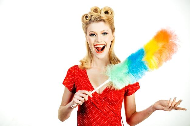 Lustige haushälterin. reinigungsservice. lächelndes mädchen mit ausrüstung für die reinigung auf weißem hintergrund, lokalisiert.