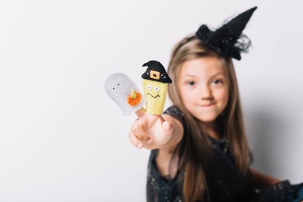 Lustige hexe, die friedensgeste mit spielwaren zeigt