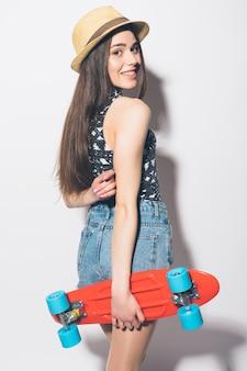 Lustige hipsterfrau mit rosa longboard isoliert