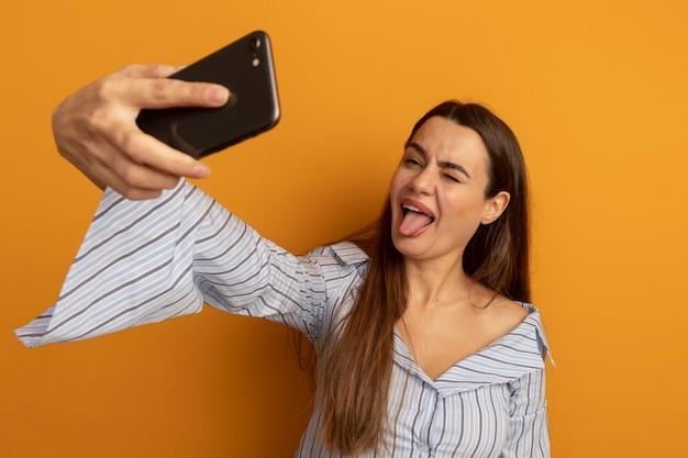Lustige hübsche frau blinzelt auge steckt zunge heraus und schaut auf telefon, das selfie lokalisiert auf orange wand nimmt