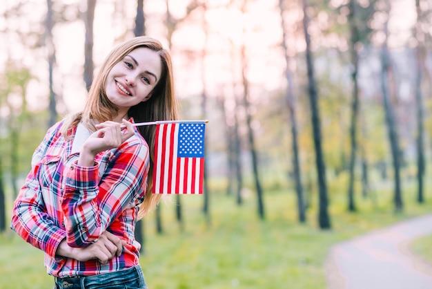 Lustige hübsche frau, die mit amerikanischer flagge aufwirft