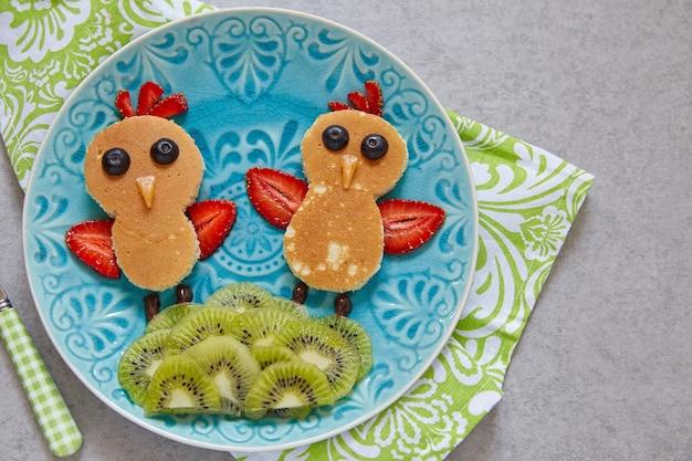 Lustige hühnerpfannkuchen mit beeren für kinderfrühstück