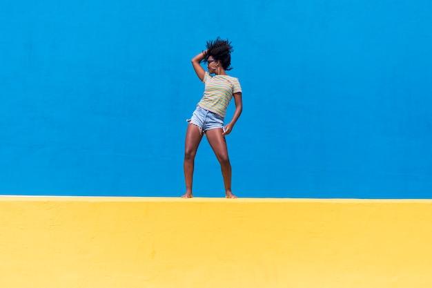 Lustige junge afroamerikanische frau, die draußen lacht und tanzt