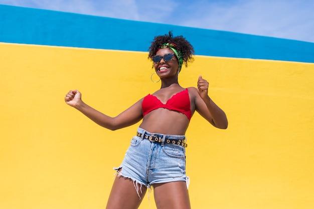 Lustige junge afroamerikanische frau, die mit erhobenen armen lacht