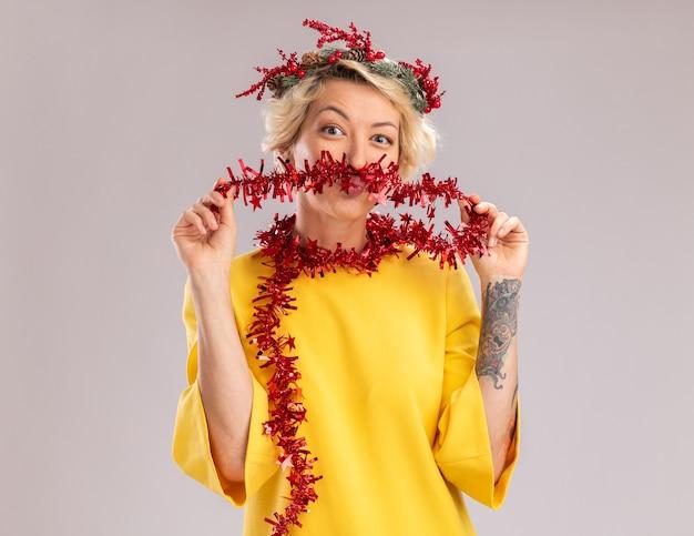 Lustige junge blonde frau, die weihnachtskopfkranz und lametta-girlande um den hals trägt und schnurrbart mit lametta-girlanden-pursierlippen isoliert auf weißer wand mit kopienraum sucht
