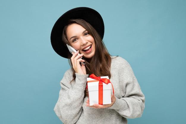 Lustige junge brünette frau lokalisiert über blauer hintergrundwand, die schwarzen hut und grauen pullover hält geschenkbox hält, die auf handy spricht und kamera betrachtet.
