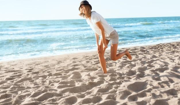 Lustige junge frau am sonnenuntergangsstrand. schöne glückliche frau am ufer des blauen meeres, positive stimmung, sommerferien, sonnig, spaßkonzept