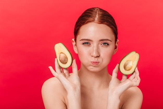 Lustige junge frau des ingwers, die avocado hält. vorderansicht des hübschen mädchens lokalisiert auf rotem hintergrund.