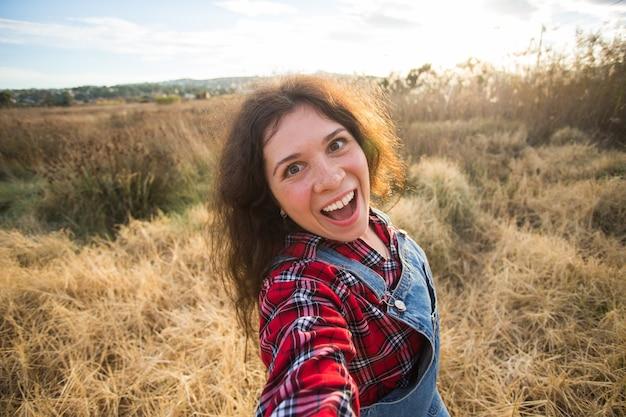 Lustige junge frau des reiseurlaubs und des feiertagskonzepts, die selfie über schöne landschaft nimmt