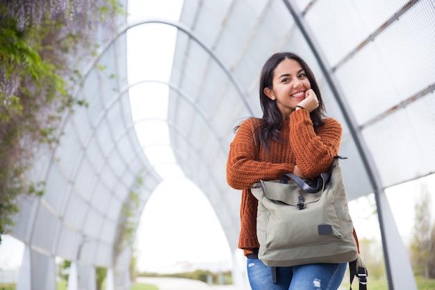 Lustige junge frau, die auf handtasche im stadtpark sich lehnt