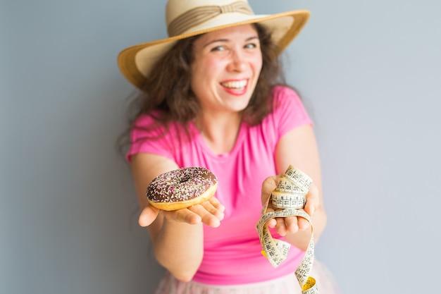 Lustige junge frau, die einen donut und ein messendes band hält. konzept von süßigkeiten, ungesundem junk food und fettleibigkeit.