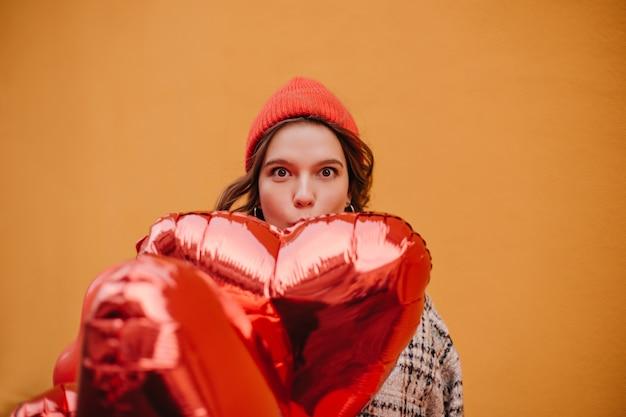 Lustige junge frau im roten hut bedeckt einen teil ihres gesichts mit dem riesigen glänzenden ballon