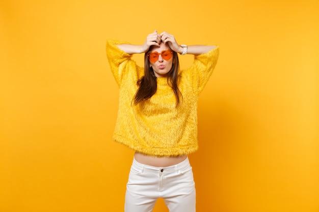 Lustige junge frau in pelzpullover herz orange brille täuschen herum blasende lippen, die hände auf den kopf einzeln auf hellgelbem hintergrund legen. menschen aufrichtige emotionen, lifestyle-konzept. werbefläche.