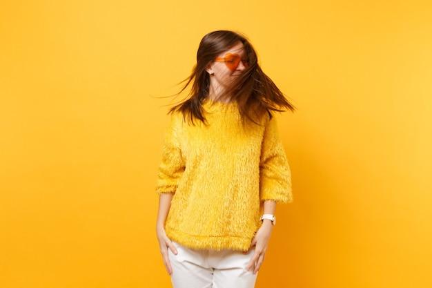Lustige junge frau in pelzpullover und herzorangefarbener brille, die im studio mit fließendem haar auf hellgelbem hintergrund herumalbert. menschen aufrichtige emotionen, lifestyle-konzept. werbefläche.