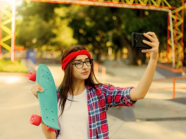Lustige junge frau mit brille und rotem kariertem hemd. hipster girl n skatepark während selfie mit skateboard im skatepark am sonnigen hellen tag macht. sommerspaß