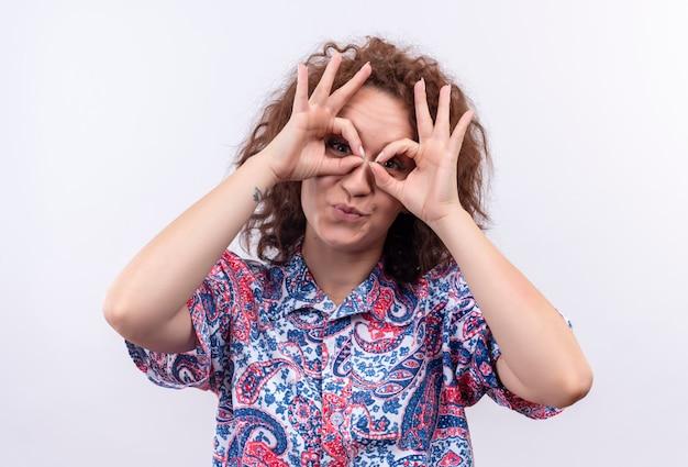 Lustige junge frau mit dem kurzen lockigen haar im bunten hemd, das ok zeichen mit fingern wie binocularr tut, die durch finger schauen