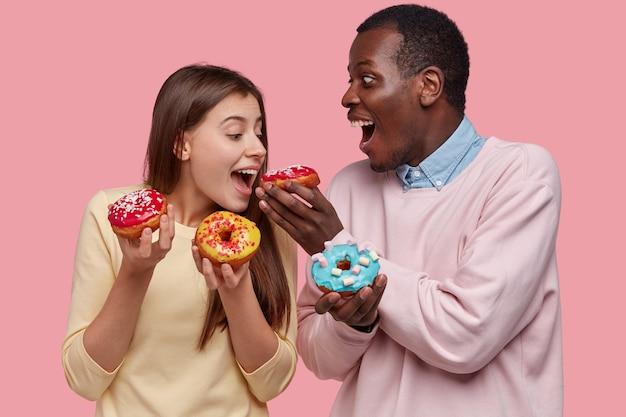 Lustige junge frau und mann der gemischten rasse schmecken köstliche donuts, wie süßes dessert, beißen gebäck, stehen eng, isoliert über rosa raum