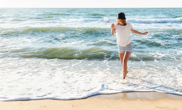 Lustige junge frau verspielt am sonnenuntergangsstrand. schöne glückliche frau am ufer des blauen meeres, die spaß spielend, positive stimmung, sommerferien, sonniges konzept hat