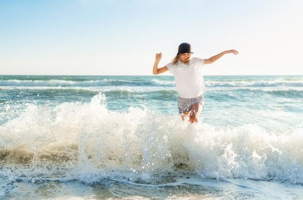 Lustige junge frau verspielt am sonnenuntergangsstrand. schöne glückliche frau am ufer des blauen meeres mit spaß beim spritzwasser, positive stimmung, sommerferien, sonniges konzept
