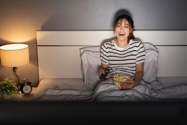 Lustige junge frau vor dem fernseher und lachend auf einem bett in der nacht