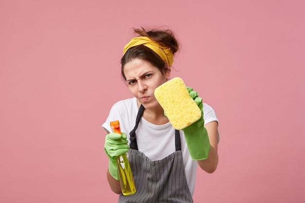 Lustige junge hausfrau, die freizeitkleidung, schürze und schützende gummihandschuhe trägt, die von sauberkeit besessen sind und mit messendem blick starren, während sie haus aufräumen, bis es glitzernd sauber ist