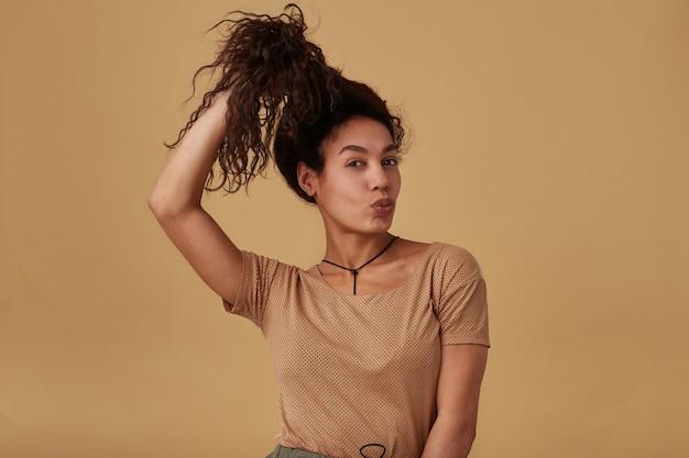Lustige junge hübsche dunkelhäutige brünette frau, die ihr lockiges haar mit erhabener hand und spitzenden lippen hält, lokalisiert auf beige