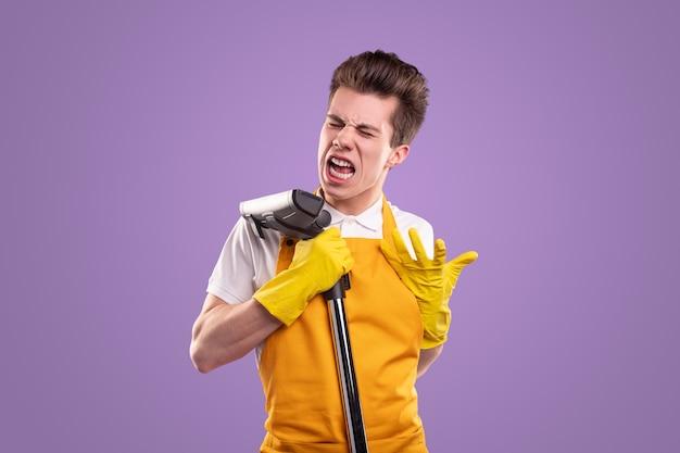 Lustige junge männliche haushälterin in schürze und handschuhen verziehen das gesicht und unterschreiben am staubsauger