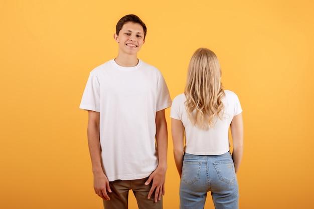 Lustige junge paare auf orange hintergrund