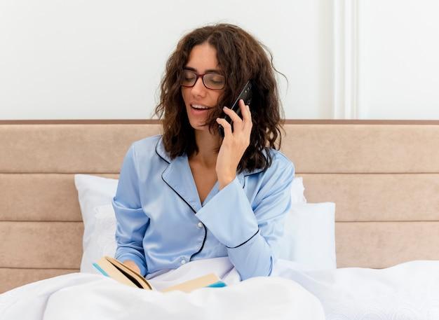 Lustige junge schöne frau im blauen pyjama, der im bett mit buch spricht, das auf handy spricht, das im schlafzimmerinnenraum auf hellem hintergrund lächelt