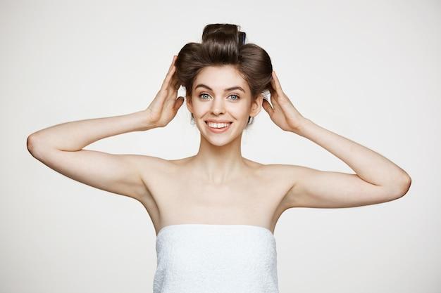 Lustige junge schöne frau in lockenwicklern und handtuchaufstellung. schönheitskosmetik und spa.