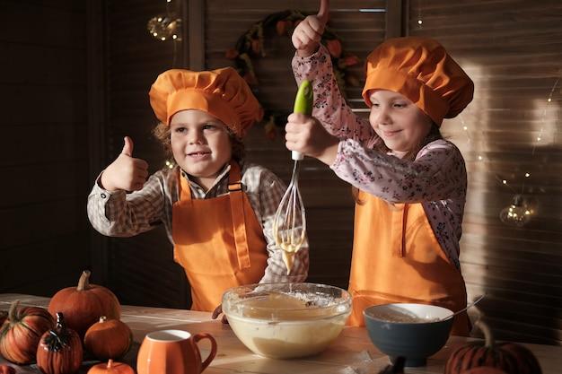 Lustige jungen und mädchen in orangefarbenen kochkostümen bereiten kürbiskuchen vor. kinder bereiten sich auf thanksgiving vor. das konzept eines familienurlaubs