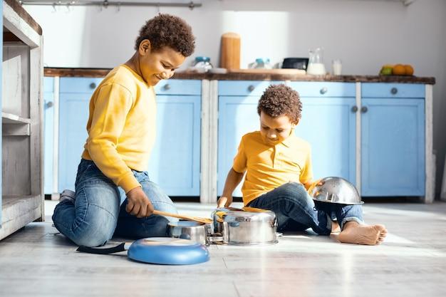 Lustige kakophonie. optimistische kleine kinder, die auf dem küchenboden sitzen und auf töpfen trommeln und sich als professionelle musiker ausgeben