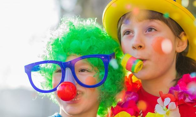 Lustige karnevalskinder lächeln und spielen im freien