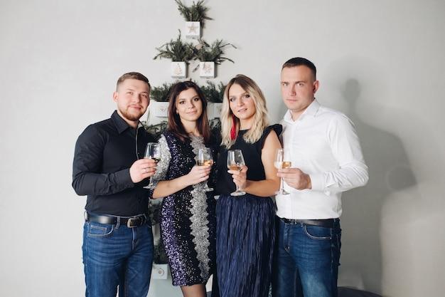 Lustige kaukasische gesellschaft von jungen kaukasischen freunden feiern weihnachten zusammen in schönen kleidern zu hause