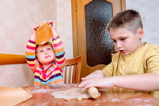 Lustige kinder backen kekse in der küche. glückliche familie.