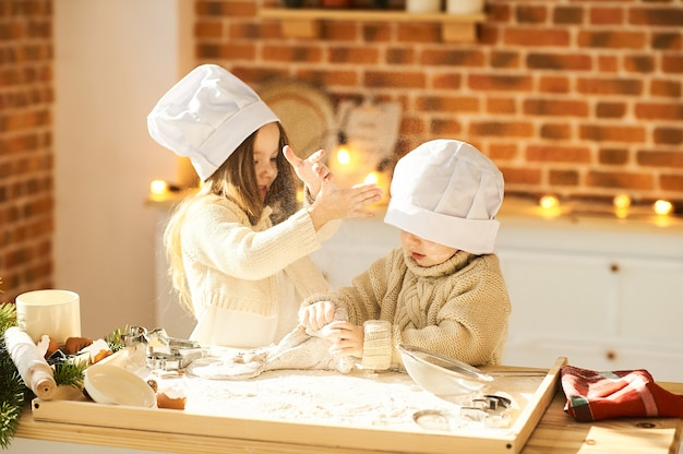 Lustige kinder der glücklichen familie bereiten den teig zu und spielen mit mehl in der küche
