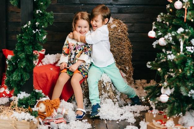 Lustige kinder, die im studio mit dekorationen des weihnachtsbaums und des neuen jahres umarmen.