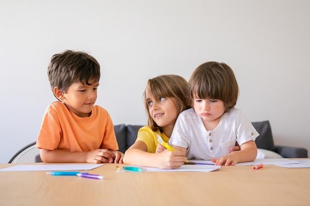 Lustige kinder, die mit markierungen im wohnzimmer malen. schönes blondes mädchen, das bruder ansieht. kinder sitzen am tisch, zeichnen mit stiften und spielen zu hause. kindheit, kreativität und wochenendkonzept