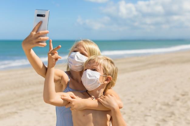 Lustige kinder, die selfie-foto durch smartphone am tropischen meeresstrand nehmen.