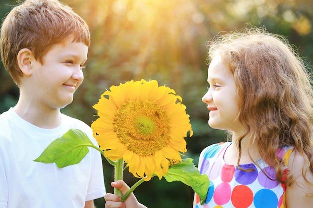Lustige kinder, die sonnenblume am sonnigen tag halten.