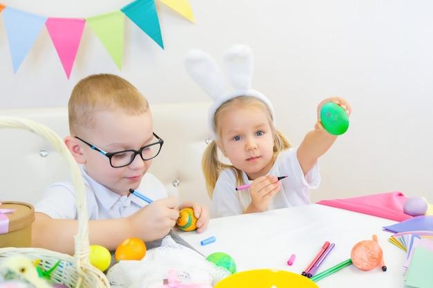 Lustige kinder in hasenohren zeichnen eier für den ostertag. kinder essen süßigkeiten und lachen. junge und kleines mädchen