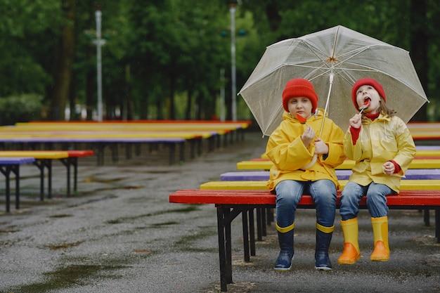 Lustige kinder in regenstiefeln, die in einem regnerischen park spielen