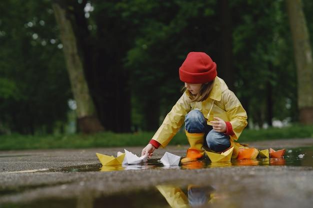 Lustige kinder in regenstiefeln, die mit papierschiff durch eine pfütze spielen
