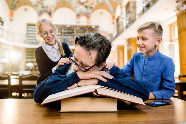 Lustige kinder, jungen und mädchen, die den bibliothekar oder großvater des älteren mannes wecken, der am tisch sitzt und auf den büchern schläft. vintage bibliothek interieur