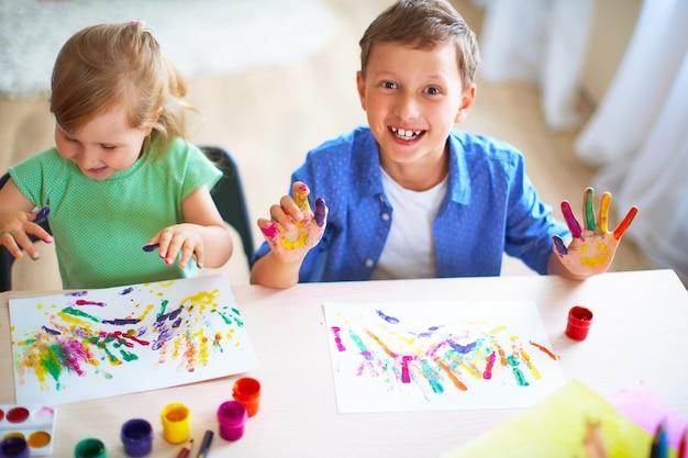Lustige kinder zeigen ihren handflächen die gemalte farbe.